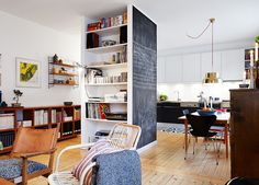 bookcase pillar in the middle of the room separates place into different zones: kitchen and living room. Love the blackboard side of shelves!