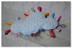Aujourd'hui je vous présente le petit nouveau dans la famille des doudous étiquettes nuages blancs avec des arabesques multicolores.