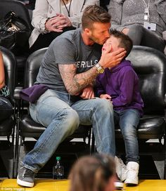 Tender moment: David Beckham planted a kiss on his youngest son Cruz as the pair watched a Lakers game in LA