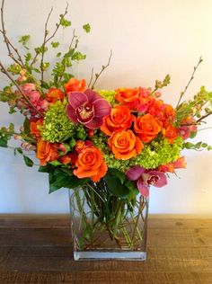 Spring mixed bouquet - Beautiful orange roses, orange and pink variegated spray roses, green hydrangea, cymbidium orchids, and quince branches. Designed by Green Bouquet Floral Design located in San Francisco Bay Area in Marin County