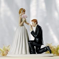 A romantic moment between bride and groom is portrayed with this cake topper as the groom kneels on one knee to kiss his bride's hand.