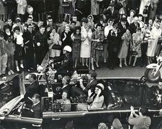 This is a really rare motorcade picture -- an aerial view of JFK's limousine in  downtown Dallas. Note that driver Bill Greer has his door open (probably  in an effort to keep the crowd back, because the police motorcycles on  the left side of the car were likely not in their normal positions when this  picture was snapped, due to the heavy crowds on that side of the street).  Also barely visible on the far right side of this photo is Secret Service agent  Clint Hill, who was riding on th