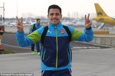 Arsenal star Alexis Sanchez poses for the cameras before boarding the flight from Luton airport