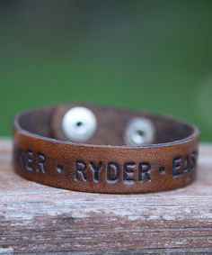 <p> handstamped thin leather cuff</p> Color: medium brown text: AWESOME (one line only)