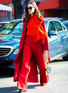A red monochromatic outfit includes a long duster coat, bow blouse, trousers, and black heels with a patterned bag
