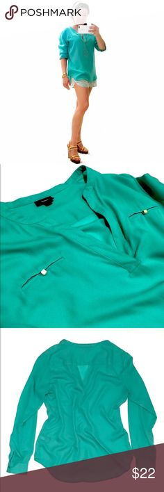 """Collarless V-Neck Turquoise Blouse w/ Gold Buttons By Mossimo. Spring season long sleeve blouse in a gorgeous light turquoise color. Light weight, flowy fabric falls nicely on the form. Size M • Bust, waist & hips are 40"""", length is 28"""". Loose fit. Perfect condition; no flaws. Small gold square buttons on front pockets • looks great tucked in with a pencil skirt or casually out with sleeves rolled up. ♥️20% off bundles of 2+♥️ Mossimo Supply Co Tops Blouses"""