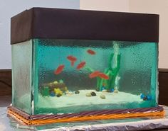 Aquarium cake! How in the world? Sheets of melted candy I bet for the glass and the fish hanging from the top. Oh how fun is that?