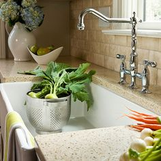 Whats Old Is New Graceful curves give the shining bridge-style faucet a vintage vibe that?s enhanced by the apron-front sink. The surrounding sand-color countertops are made of 75 percent recycled materials, including mirror, glass, porcelain, and earthenware.