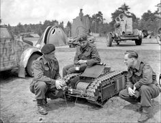 Canadian troops examine captured German equipment including a Goliath wire controlled mine tank. Despite thousands of Goliaths available to them as a beach defense the Germans inexplicably failed to use them against the allies.
