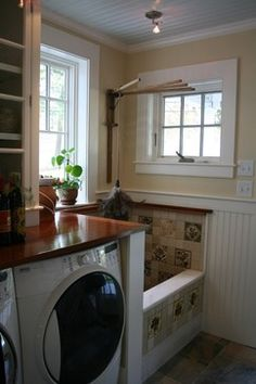 Ackerman Residence Renovation/Addition Norwich VT traditional laundry room - love the wood top over washer and dryer, and the dog wash station!  would have a simple subway tile vs the pattern tile but what a smart design!