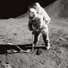 Astronaut James B. Irwin, lunar module pilot, uses a scoop to dig out a trench in the lunar soil during Apollo 15 extravehicular activity (EVA) 1971.  Mount Hadley rises approximately 14,765 feet (about 4,500 meters) above the plain in the background.