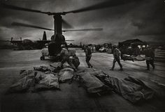 Helicopter with bay door open, bodies on stretchers on the airstrip, and Marines carrying bodies toward the helicopter.