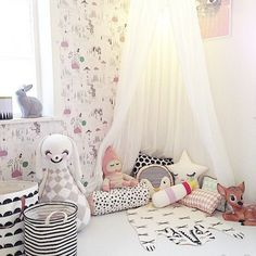 Darling wallpaper with soft toys and scatter make the perfect reading corner.