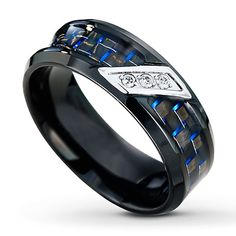 This black stainless steel wedding band for him is decorated with blue accents for a unique look. Three round diamonds are diagonally set into white stainless steel for a bold contrast. The ring has a total diamond weight of 1/20 carat. By Kay Jewelers yourdiamondteacher.com