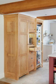 This kitchen is in perfect harmony with the classical traditional architecture of this period farmhouse. However function is as important as form and the furniture hides many modern integrated appliances such as this larder unit with its hidden fridge / freezer and microwave