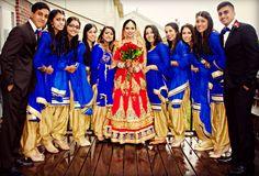 Indian Sikh Punjabi bride with bridesmaids in royal blue suits bridesmen. Wedding