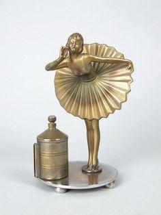 Austrian spelter striker with a saucy dancer, designed by Stephan Dakon. In the barrel to the side of her is the striker (cigarette lighter)