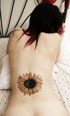 Tattoo sexy fleur de tournesol sur le bas du dos d'une femme https://tattoo.egrafla.fr/2016/02/02/modeles-tatouage-tournesol/