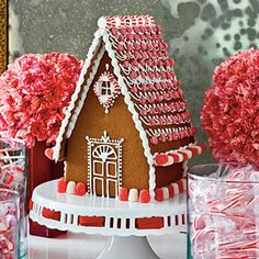 A gingerbread house trimmed in red and white candies gives a touch of whimsy to a sophisticated setting. For extra height, display it on a cake stand.
