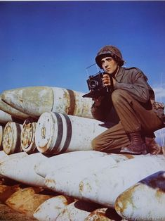 Crouching on 16-inch shells used in the coastal defense guns at Viareggio, Italy, is a still photographer with the 196th Signal Photo Company.