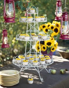 Miniature sunflower cupcakes on an antique wire stand encourage guests to help themselves between dances. Lanterns suspended from tree branches light the way after sundown.   - CountryLiving.com