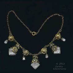 A superb vintage 1920's to 1930's necklace of yellow brass and faceted clear glass stones set in brass bevels.  There are layers of brass filigree flowers that overlap the beveled stones.  clear crystal glass drops with brass bead caps alternate with the glass stones.  There are small clear glass rhinestones in the alternating brass flower links and the centers of the filigree flowers.  Finished with a brass rectangular cable chain.