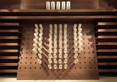 The wooden wine cellar, closed by made to measure sliding doors, has inclined central elements and horizontal shelves with curved trays to house the bottles.