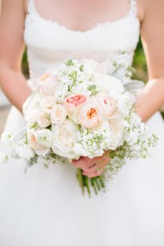 a beautiful garden inspired brides bouquet of white ranunculus, white o'hara garden rose, soft peach juliette garden rose, white sweet pea, white stock, dusty miller and seeded eucalyptus.