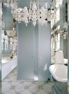 Glamorous bathroom with mirrored walls and ceilings adorned with Baccarat crystal wall sconces and chandelier. A pair of frosted glass doors centered on the inset mirrored walls leads to the walk-in shower. The silver leafed freestanding bath tub sits in the mirrored nook beside the shower doors. The floor is tiled in a mini mosaic tiled laid in a diamond trellis pattern.