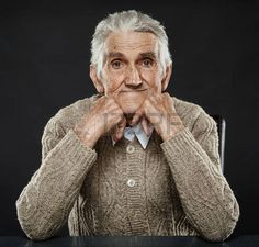 Happy 80 years old man sitting at the desk, studio shot photo