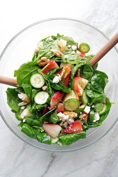 Strawberry Cucumber Spinach Salad with Apple Cider Vinaigrette in a large glass bowl with two wooden spoons.