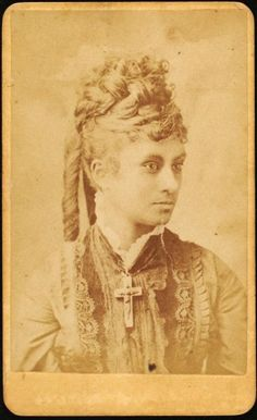 ca. 1860-90s, [carte de visite portrait of a young women wearing a large cross and a gorgeous dress], Henrici & Garns via the New York Public Library, Schomburg Center for Research in Black Culture, Photographs and Prints Division