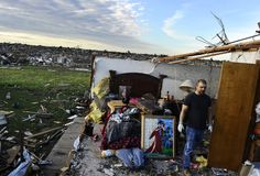 A man salvages stuff from what left of a bedroom of his tornado devastated home on May 21, 2013 in Moore, Oklahoma. Families returned to a blasted moonscape that had been an American suburb Tuesday after a monstrous tornado tore through the outskirts of Oklahoma City, killing at least 24 people. Nine children were among the dead and entire neighborhoods vanished, with often the foundations being the only thing left of what used to be houses and cars tossed like toys and heaped in big piles…