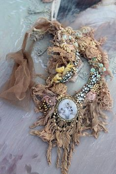 Experimental necklace in my original style,-series with old laces& hand embroidery inspired by antique laces and vintage finds. Shades of beige, sand, cream.. This shabby chic detailed neckpiece is made of wide array vintage and antique textiles. The bold necklace has rustic, tattered