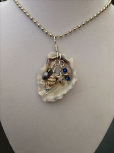 Seashell pendant with wire wrapped charms and pearls.