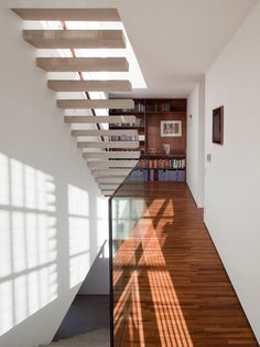 Concrete staircase, glass balustrade,  shadow gap at skirting level, wood flooring...nice to see all of them in the same image!    Concrete – House 6 – Marcio Kogan
