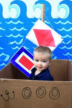 """""""I wanted to have some kind of boat for the kids to play in. I just constructed this out of cardboard. I added a couple of these flags. The backdrop was made from this. """""""