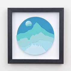 9x9 glass framed original art. Diorama styled or 2d papercuts layered with paper to make 3d. The shapes are hand cut and then glued together. The image is of a mountain with the hills leading up to it in shades of blue. Its like looking at a mountain at a distance before the sun casts its rays. No actual mountains were deliberately depicted in the making of this art piece. Picture taken without glass to reduce glare. Product comes glass framed.