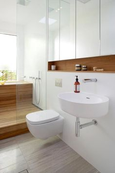 Nice wet room to the side in design - I also like the combination of white fixtures, wood for warmth and the grey tiles.