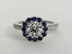 Enduring and elegant, this halo sapphire and diamond engagement ring features a frame of blue sapphires contrasted with pavé-set diamonds along the 18k white gold ring design. #bluenile
