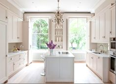 White kitchen, white counters and cabinets, large windows and high ceilings bring in tons of natural light
