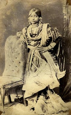 A gharara is a traditional Lucknowi garment, traditionally worn by Muslim women of Hindi Belt It consists of a kurti (a short, mid-thigh length tunic), a dupatta (veil), and most importantly, a pair of wide-legged pants, ruched at the knee so they flare out dramatically. The knee area, called the goat in Urdu, is often elaborately embroidered in zari and zardozi work. Each leg of a traditional gharara is made from over 12 metres of fabric often silk brocade