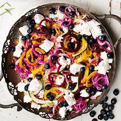 Med en grönsakssvarv gör du snabbt snygga strimlor av olika slags betor och zucchini. Använd annars en osthyvel eller mandolin. Blanda den krispiga grönsakspastan med blåbär, fetaost och en god vitlöksdressing. Modern råkost och en fröjd för ögat!