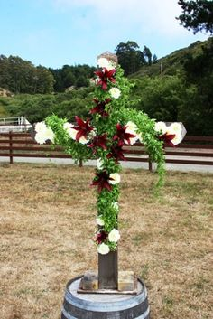 A historic wooden cross from a 1900's church is decorated with flowers and vines at a pasture wedding at Long Branch Saloon and Farms in Half Moon Bay, CA. Photo courtesy of Joe Ripp Photography. Flowers by Seasonal Celebrations, http://www.seasonalcelebrations.com