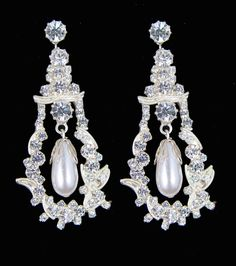 Queen Mary's Pendant Earrings: They were converted from a pendant necklace by Queen Mary.  Each has an oval pearl suspended from a collet diamond hanging in an ornate frame design set in diamonds.