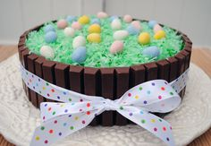 Easter Kit Kat Cake Ingredients:     your favorite cake   your favorite icing   22 (.49 oz. size) Kit Kat bars (I bought 3 packs of 8 of the snack size)   coconut (I used about 1/3 to 1/2 of a 14 oz. bag)   green food coloring   Cadbury Mini Eggs   ribbon