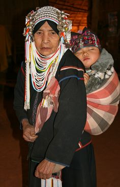 Akha hilltribe woman in traditional clothing carrying a sleeping baby on her back. Near Chiang Rai in Northern Thailand
