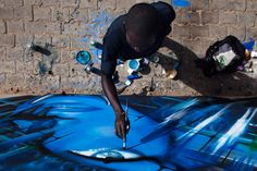 graffiti artist Chimere paints a mural next to a highway in Dakar.