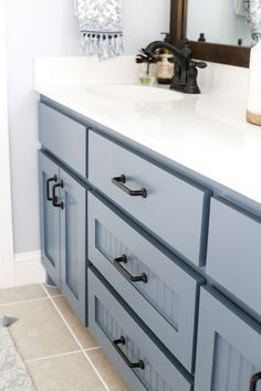 Basic builder bathroom cabinets get new life with a contemporary paint color and new hardware. Click this pin to see the dramatic master bath update!