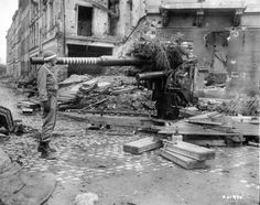 """An American MP examines a German 88mm anti-aircraft FlaK 18 used as an anti-armor gun (1945). The barrel's painted rings indicate 11 destroyed units. In the background are spent shell cases. The inscription on the wall reads """"Gaststätte"""", for café-restaurant."""